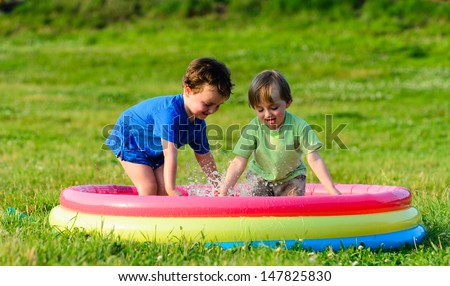 Two young boys playing in a paddling pool together in the summertime - stock photo