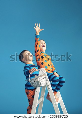 Two young boys reaching stars - stock photo