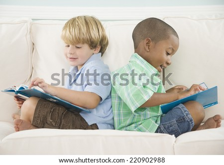 Two young boys reading on sofa - stock photo