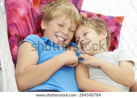 Two Young Boys Relaxing In Garden Hammock Together