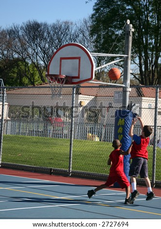 Two young boys shooting some hoops at the park