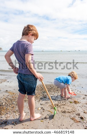 Two young boys standing and playing on the beach