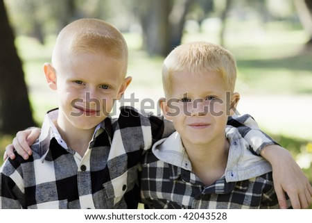 Two Young Brothers Arm in Arm Smiling To The Camera