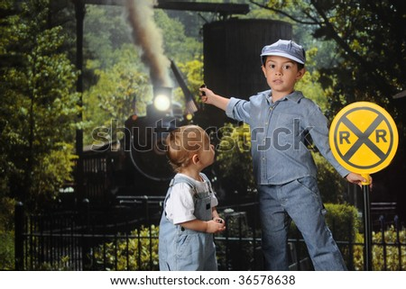 Two young brothers in train engineer outfits, one warning viewers of an approaching train. - stock photo