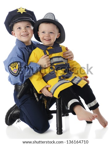 Two young brothers posing together -- an elementary boy in a policeman's outfit, the toddler dressed as a fire fighter.  On a white background. - stock photo