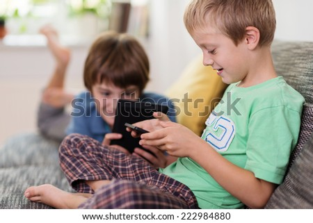 Two young brothers relaxing with their tablets on a comfortable sofa at home smiling as they read an e-book or surf the internet - stock photo