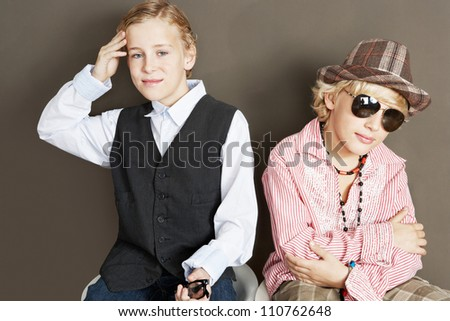 Two young brothers sitting together showing attitude and different personalities.