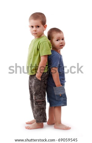 Two young brothers standing back to back. - stock photo