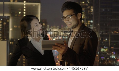 two young business coworkers looking at tablet computer screen talking together. asian man having a conversation with a caucasian women. professionals meeting scene
