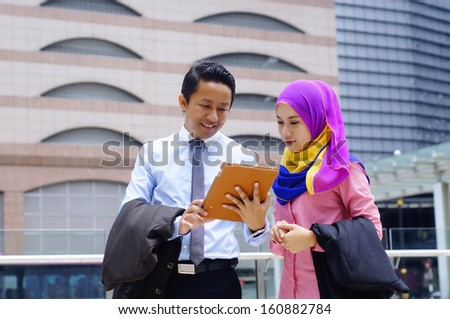 Two young business executives using tablet computer outdoors