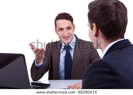 two young business men having a discussion at their desk - stock photo