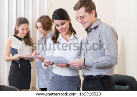 Two young business partners discussing documents in office - stock photo