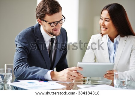 Two young business partners working together and using touchpad - stock photo