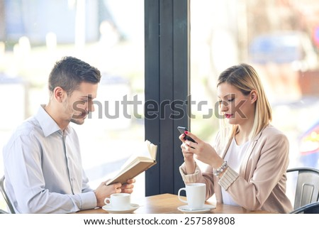 Two young business people are sitting in a cafe. Young man's reading a book and young woman's using smart phone. - stock photo