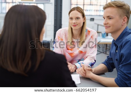 Two young business people in a meeting with their manageress or supervisor listening as she speaks to them in an over the shoulder view
