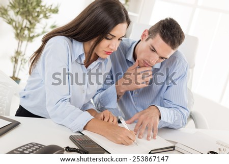 Two young business people, man and woman sitting in office at an office desk and looking at the organiser in which businesswoman writes.