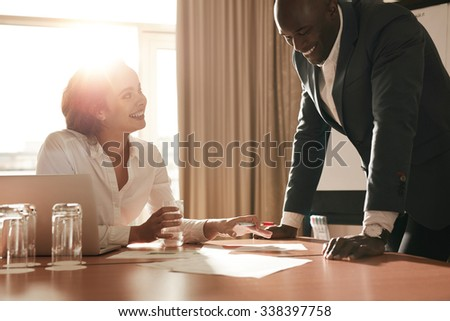 Two young business people meeting in conference room and working on new projects. Happy coworkers discussing new business ideas. - stock photo