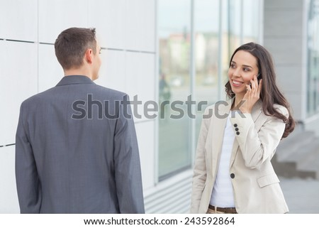 Two young business people meeting in front of the office - stock photo