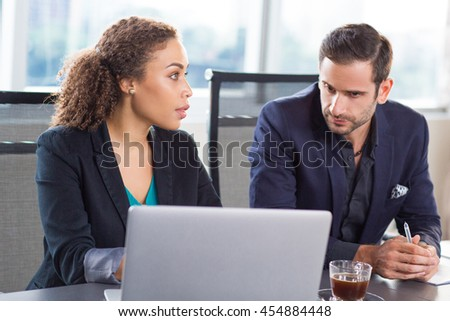 Two young business people sitting at desk in office - stock photo