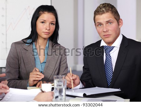 Two young business people sitting at table and work on some paperwork - stock photo
