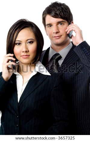 Two young business people with mobile phones on white background