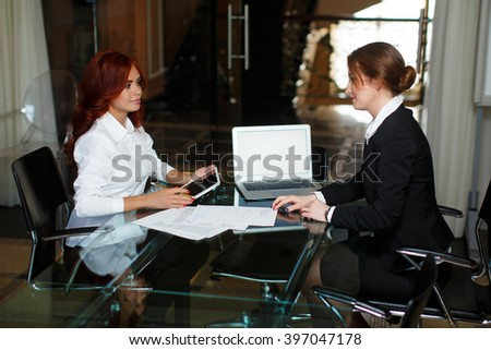 two young business woman holding talks in the office - stock photo
