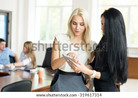 Two young business woman with tablet computer in the office to discuss the problem at a business meeting. - stock photo