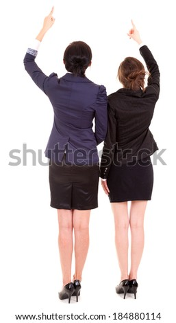 two young business women standing back andpointing up, white background - stock photo