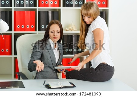 Two young business women  with computer tablet and daily log sit in the office. - stock photo