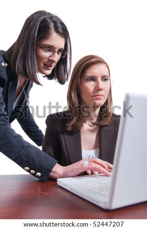 Two young business women working on the laptop.