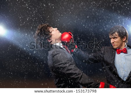 Two young businessman boxing againts dark background . conceptual collage - stock photo