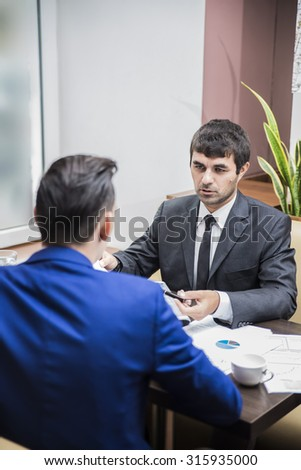 two young businessman happily discussing the case in a coffee shop