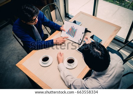 Two young businessmen are chatting in a coffee shop.