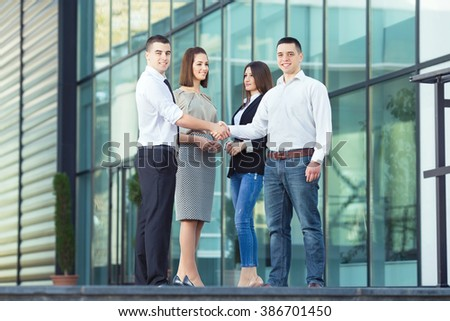 Two young businessmen are shaking hands in front of the office building. Two young businesswomen are standing next to them in the background.