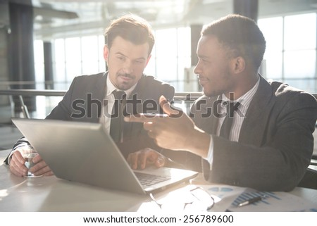 Two young businessmen are working with laptop in modern office. - stock photo