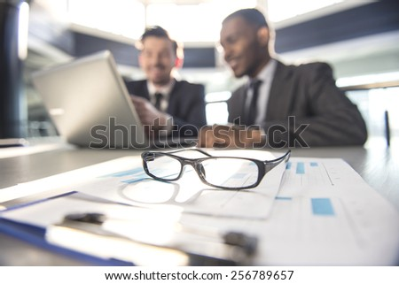 Two young businessmen are working with laptop in modern office.