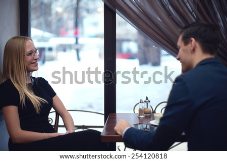 Two young businessmen during lunch in the cafe have a small talk smiling. - stock photo
