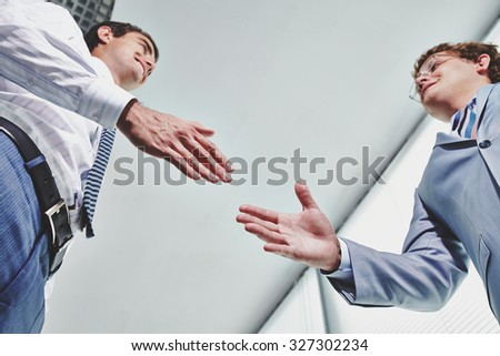Two young businessmen greeting one another by handshake - stock photo