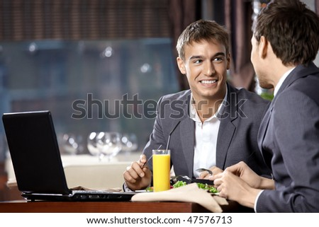 Two young businessmen have supper at restaurant - stock photo