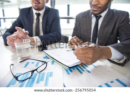 Two young businessmen in the modern office at work are discussing something. Focus on the things on the table. - stock photo