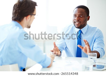 Two young businessmen interacting in office - stock photo