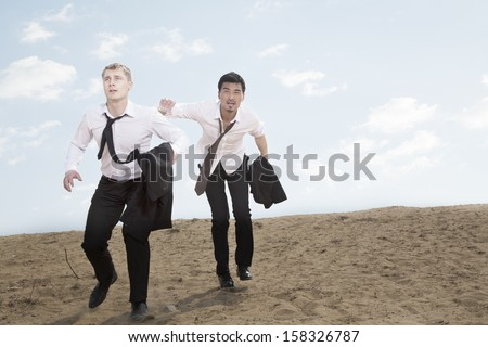 Two young businessmen running and exhausted in the desert