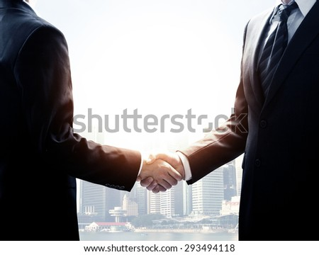 two young businessmen shaking hands on city background - stock photo