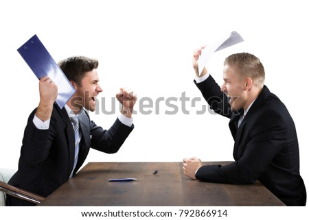 Two Young Businessmen Shouting At Each Other On White Background