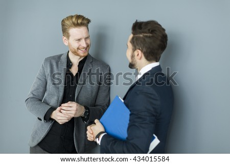 Two young businessmen talking in the office - stock photo