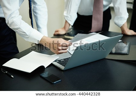 Two young businessmen using laptop at meeting - stock photo