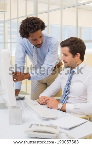 Two young businessmen working on computer in the office