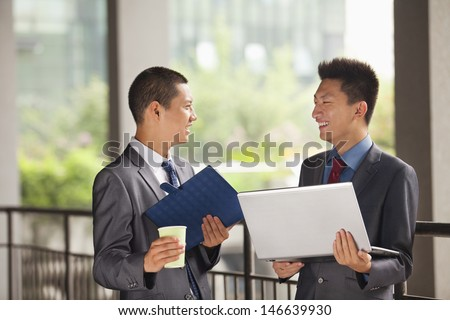 Two young businessmen working outdoor, looking at each other - stock photo