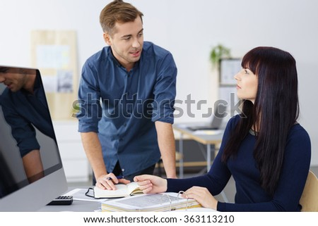 Two young businesspeople in a meeting having a serious discussion over paperwork as the young woman looks up to the man leaning over her