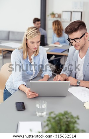 Two Young Businesspeople Reading Something at the Laptop Computer Together While Having a One-on-One Business Meeting. - stock photo